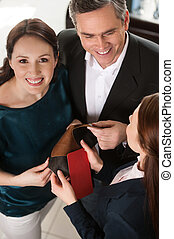 Couple in furniture store. Top view of cheerful middle-aged couple choosing fabric and communicating with sales clerk