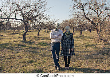 Couple in gas mask among cut trees - Couple in gas mask...