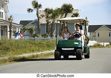 Caucasian mid-adult man and woman driving golf cart down residential street.