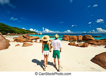 Couple in green on a tropical beach at Seychelles