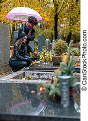 Couple in grief on a cemetery in fall