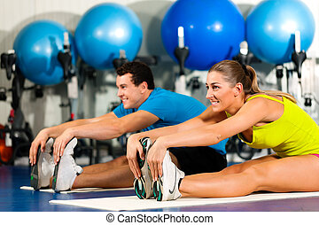 couple in colorful cloths in a gym doing aerobics or warming up with gymnastics and stretching exercises
