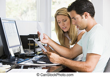 Couple in home office with computer and paperwork looking...
