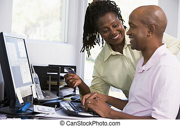 Couple in home office with credit card using computer and smilin