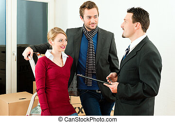 Young couple buying or renting a home or apartment, they are meeting the owner or real estate broker negotiating details