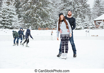 Couple in ice skates standing outdoors