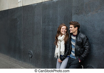 Couple In Jackets Leaning On Wall