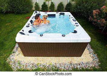 Happy couple relaxing in jacuzzi. Vacation concept.