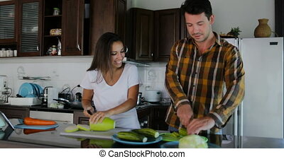 Couple In Kitchen Cooking Together, Woman And Man Talking Cut Vegetables To Prepare Healthy Dinner