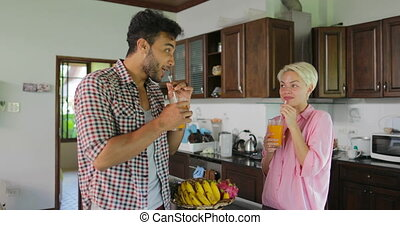 Couple In Kitchen Drink Orange Juice In Morning, Young Man And Woman Talking Breakfast