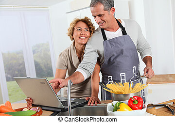 Couple in kitchen looking at recipe on internet