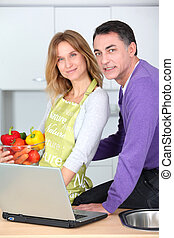 Couple in kitchen looking for cooking recipe