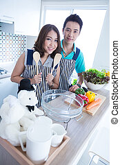 couple in kitchen - Young happy couple prepare vegetable...