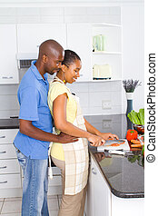 couple in kitchen preparing food