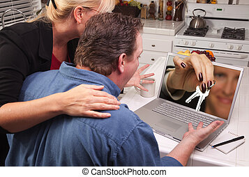 Couple In Kitchen Using Laptop - House Keys