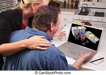 Couple In Kitchen Using Laptop - Online Poker