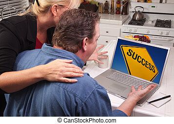 Couple In Kitchen Using Laptop - Success Sign