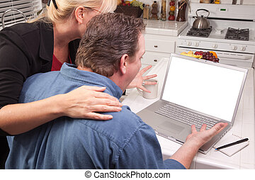 Couple In Kitchen Using Laptop with Blank Screen