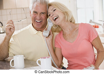 Couple in kitchen using telephone together and laughing