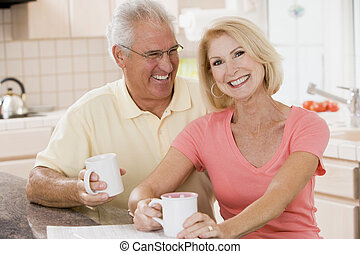 Couple in kitchen with coffee smiling