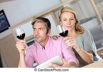 Couple in kitchen with glass of wine web surfing on tablet