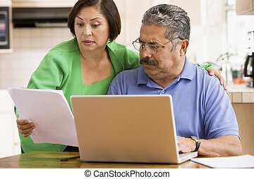 Couple in kitchen with laptop and paperwork
