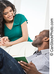 Couple in living room talking while sitting on sofa. profile of black african man sitting on sofa and looking at woman