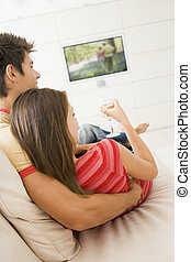 Couple in living room watching television and drinking white win