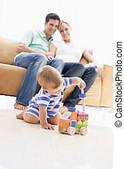 Couple in living room with baby smiling