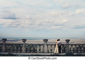 Couple in love admires gorgeous sky from the ruined stone balcony