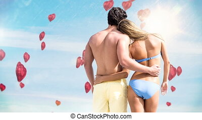 Couple in love admiring the sky on the beach