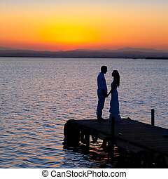 couple in love back light silhouette at lake sunset full...