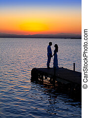 couple in love back light silhouette at lake