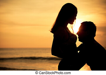 couple in love back light silhouette on sea at the sunset time