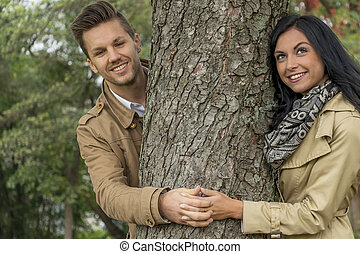 couple in love behind a tree - a young, lost couple looks...
