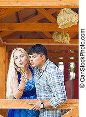 Couple in love blowing dandelion on a summer day