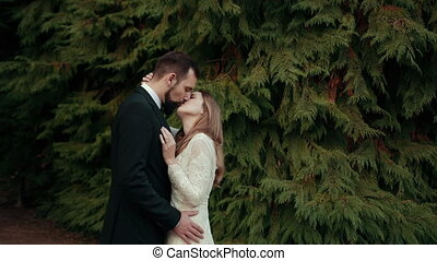 Young couple in love bride groom in wedding white dress black suit hug, sniff each other and kiss. The woman gently holds man's neck with her hand. On background of Christmas trees