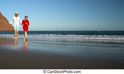 Couple in love carefree running along the beach. Picturesque ocean coast of Tenerife, Canarian Islands, Spain