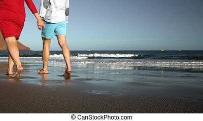 Couple in love carefree walking along the beach. Picturesque ocean coast of Tenerife, Canarian Islands, Spain