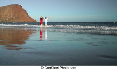 Couple in love carefree walking to the water on the beach....