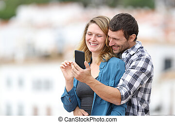Couple in love checking mobile phone in a rural town