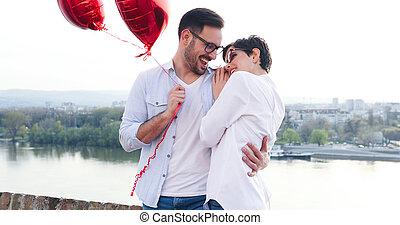 Couple in love cuddling while enjoying beautiful urban sunset together