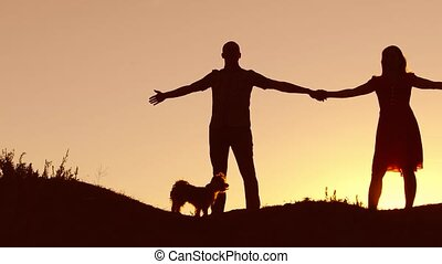 Couple in love dancing silhouette at sunset and kissing. Loving man and woman with dog dancing silhouette slow motion video