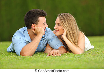 Couple in love dating and looking each other lying on the grass with a green background
