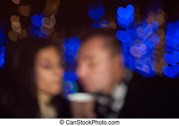 couple in love drinking latte on a background of blue hearts