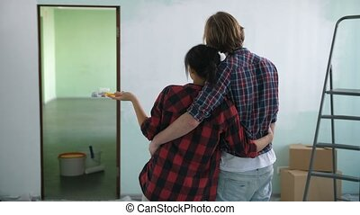 Couple in love embrace looking at painted wall