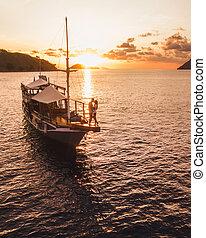 Couple in love enjoying sunset on yacht board