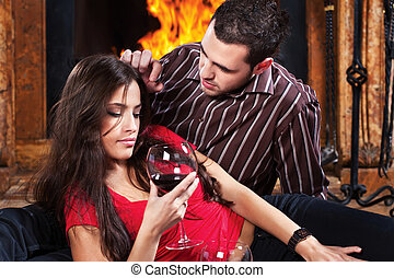 couple in love enjoying wine near fireplace