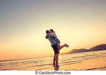 Couple in love having romantic tender moments at sunset on the beach.