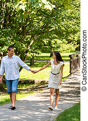Couple in love holding hands walking park